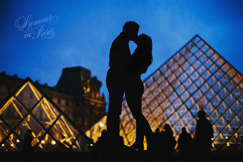 Romantic couples portrait session of Allison Morton and Ahmed Soualhi in Paris France in the courtyard of the Louvre pyramid at night by Paris portrait photographer Stacy Reeves for L