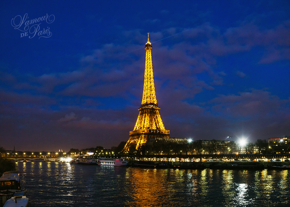 Eiffel Tower at night reflecting on the Seine River