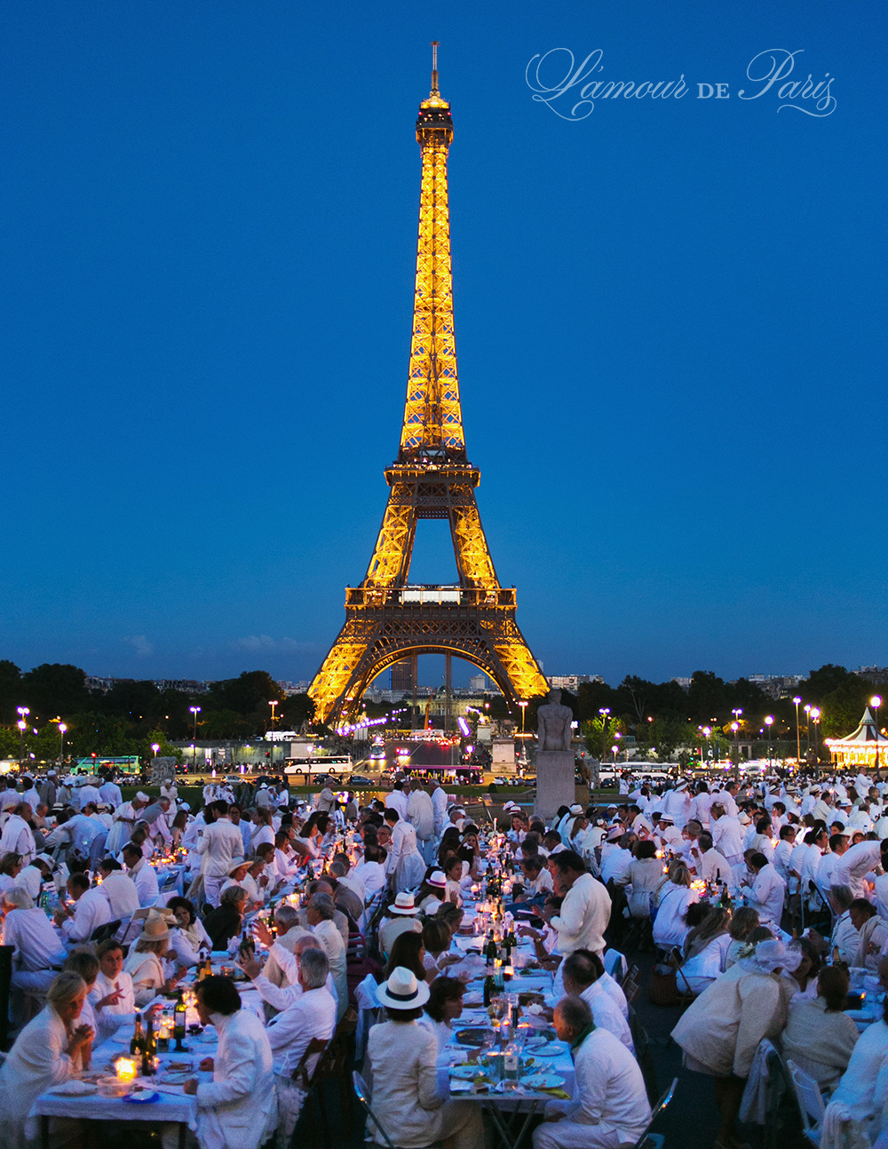 Diner en Blanc, also known as Diner in White, a top secret invitiation-only flash mob in Paris, France where 11,000 people dressed entirely in white clothes spontaneously set up tables and chairs in front of historic landmarks one night a year. The 2013 Diner en blanc, held on July 13, took place in the Louvre courtyard and by the Trocadero fountains in front of the Eiffel Tower. Photographed by Paris wedding and portrait photographer Stacy Reeves for vacation planning blog L