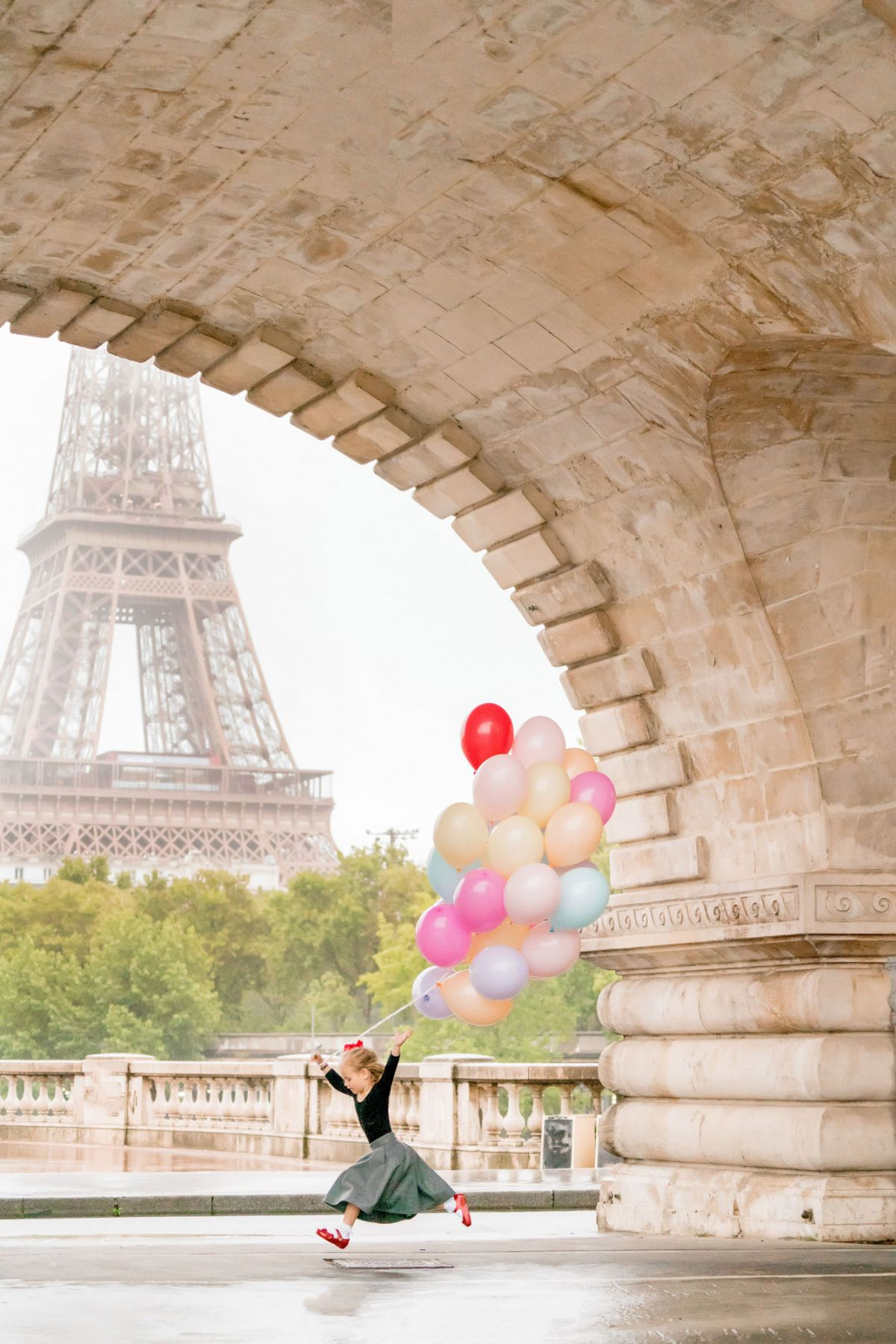 Paris family photo session at eiffel tower little girl with a bundle of colorful balloons