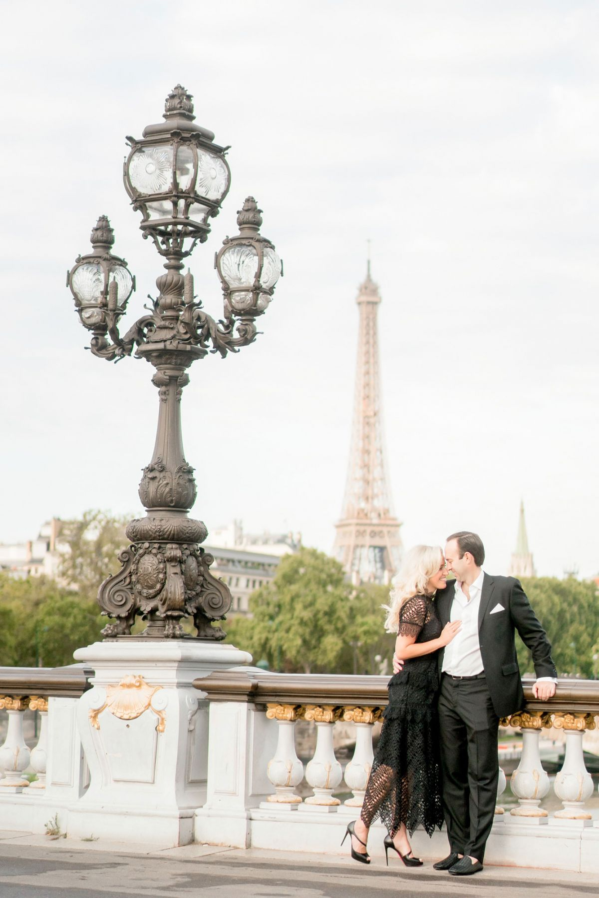 couple snuggles on pont alexandre bridge in paris